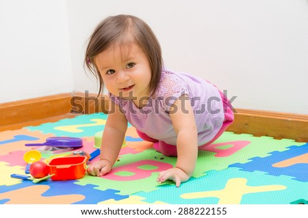 Adorable baby girl playing on child friendly floor mats crawling and looking at camera - stock photo