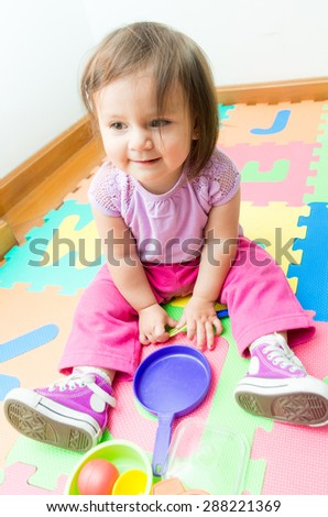 Adorable baby girl playing on floor mats with plastic toys - stock photo