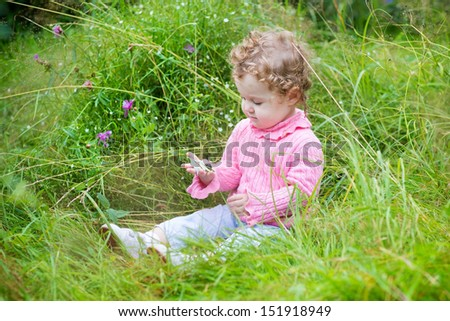 Adorable baby girl playing with a snail in the garden among beautiful wild flowers - stock photo