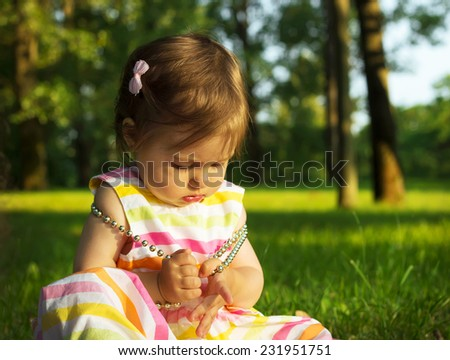 Adorable Baby Girl playing with beads - stock photo