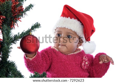 Adorable baby girl playing with christmas tree over white background