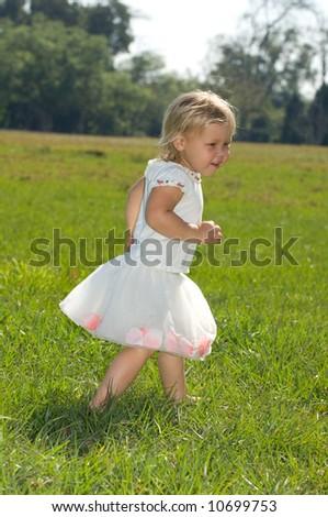 Adorable Baby Girl Running in Field in Tutu - stock photo