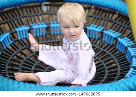 Adorable baby girl sitting in a rubber net swing at a playground