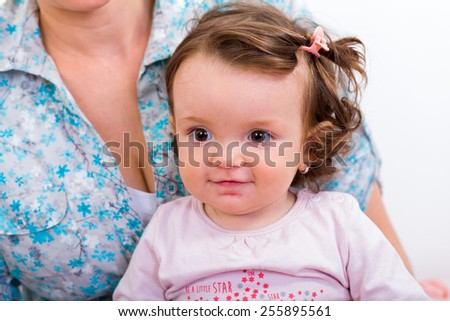 Adorable baby girl sitting in her mother lap - stock photo