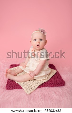 Adorable baby girl sitting looking at the camera, child development milestone - stock photo