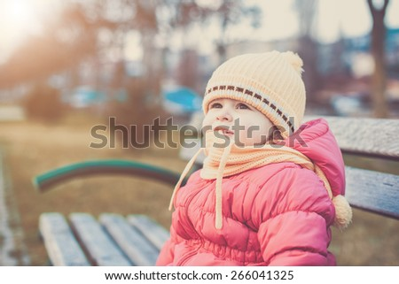 adorable baby girl sitting on a bench in the park in winter clothes - stock photo