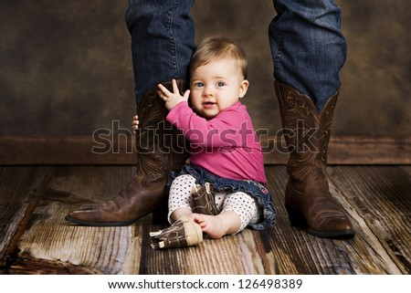 Adorable baby girl sitting on the floor holding her mothers leg. - stock photo