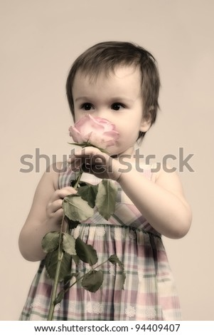 Adorable baby girl smelling flower, sepia toned - stock photo