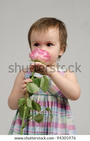 Adorable baby girl smelling pink rose flower - stock photo