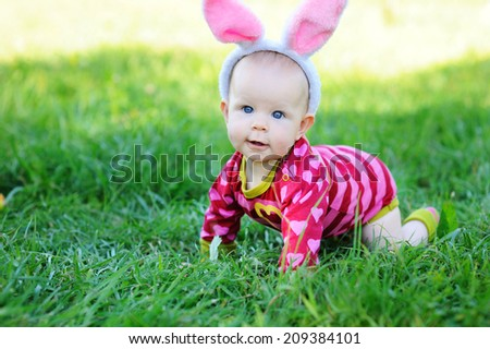 Adorable baby girl wearing bunny ears on the green lawn in the sunny day - stock photo