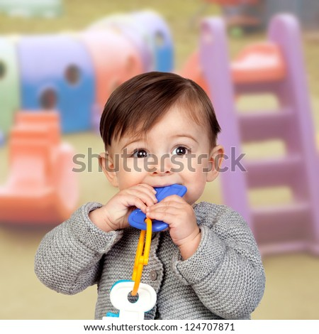 Adorable baby girl with a bite in her mouth - stock photo