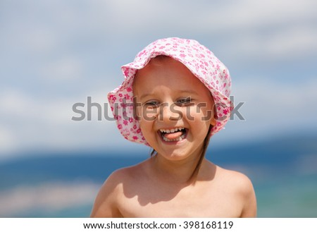 Adorable baby girl with a hat on his head on a blurred background of blue sky and sea. Laughing happy child. Hot sunny summer day. Selective focus. - stock photo
