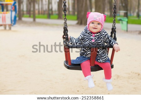 Adorable baby girl with big beautiful eyes having fun on a swing ride at a playground in a sunny summer park - stock photo