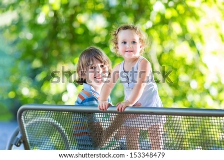 Adorable baby girl with curly hair wearing a blue dress playing with her brother sitting on a bench in a sunny summer park at a river shore - stock photo