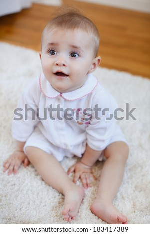 Adorable baby girl with curly hair wearing a dress playing on the floor
