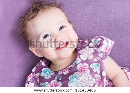 Adorable baby girl with curly hair wearing a purple dress - stock photo