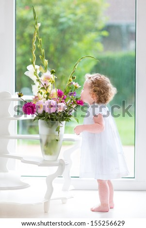 Adorable baby girl with curly hair wearing a white dress smelling beautiful flowers next to a wind and door to the garden - stock photo