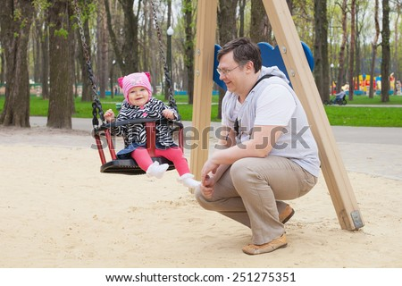 Adorable baby girl with father having fun on a swing ride at a playground in a sunny summer park - stock photo