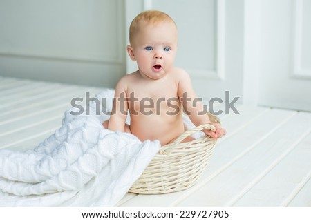 adorable baby girl with fun emotions sitting in basket with blanket at white interior - stock photo