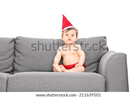 Adorable baby girl with santa hat seated on a sofa isolated on white background - stock photo