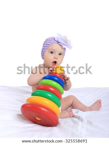 Adorable baby girl with toy on blanket on a white background