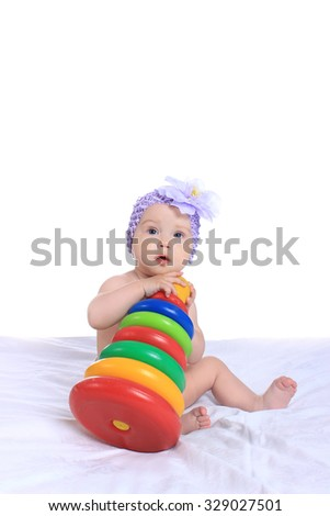 Adorable baby girl with toy on blanket on a white background - stock photo