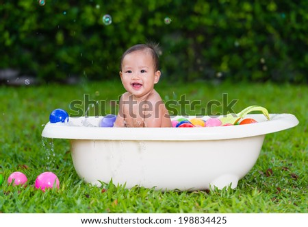 adorable baby having bath in tub at outdoor - stock photo