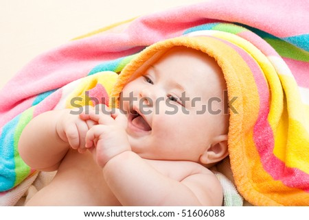 Adorable baby in colorful towel after bath - stock photo