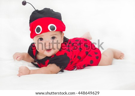 Adorable baby in dress ladybug red happy on the bed. - stock photo