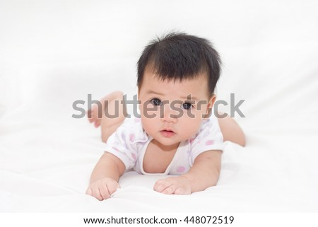 Adorable baby in dress white happy on the bed.