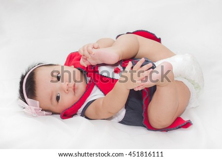Adorable baby in sailor suit look suspicion on the bed.