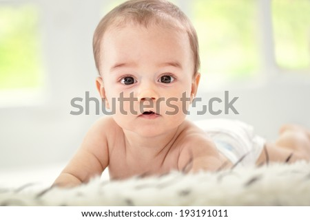 Adorable baby lies and looking forward - stock photo