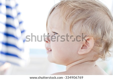 Adorable baby looking aside. Face of cheerful amazing girl. Charming curly blonde toddler with blue eyes and perfect nose having rest on the seaside. Happy careless childhood. Colorful picture. - stock photo