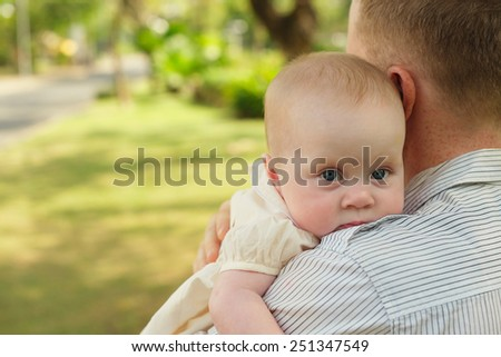 Adorable baby looking over shoulder of her father - stock photo