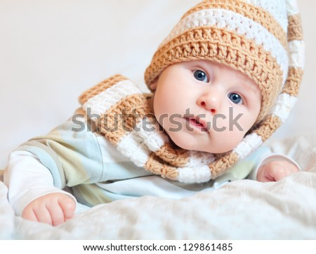 Adorable baby lying in knitted hat - stock photo