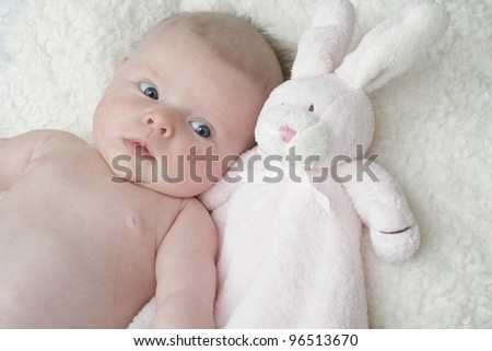 Adorable baby lying on soft furry blanket cuddling with pink toy bunny rabbit. Horizontal layout with copy space.