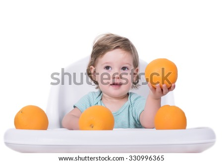 Adorable baby offering orange, healthy food concept - stock photo