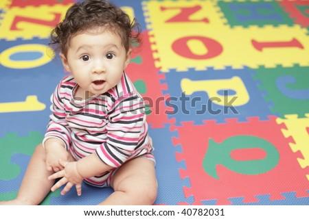 Adorable baby on a alphabet play mat - stock photo