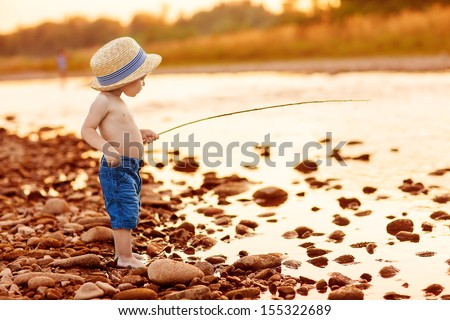 Adorable baby on river with fishing-rod and fishing - stock photo
