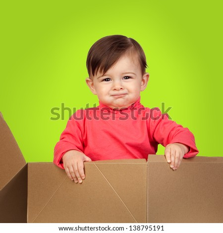 Adorable baby out of a package on a green background - stock photo