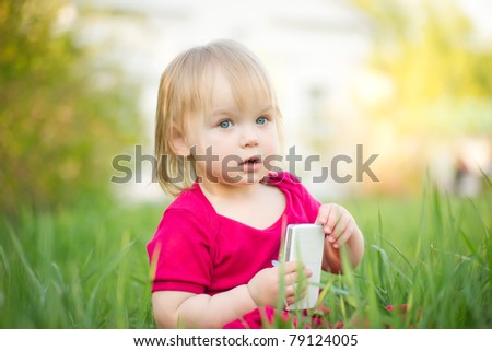 Adorable baby play with cell phone sitting in deep grass in park - stock photo