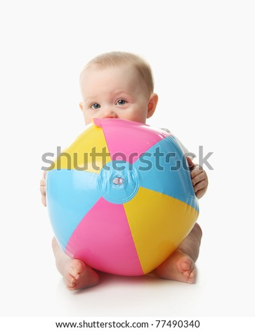 Adorable baby playing with a colorful beach ball, isolated on white - stock photo