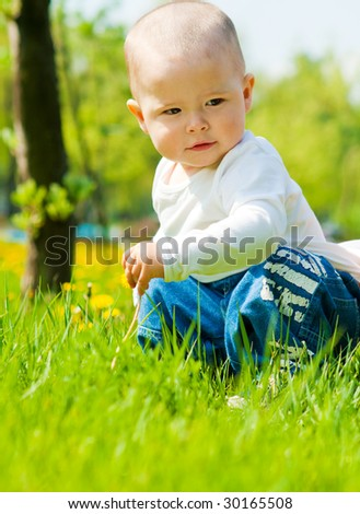 Adorable baby playing with dandelions in the park - stock photo