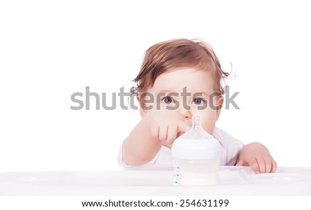 Adorable baby pointing on baby bottle with milk - stock photo