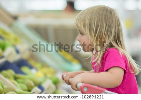 Adorable baby sit in cart in supermarket - stock photo