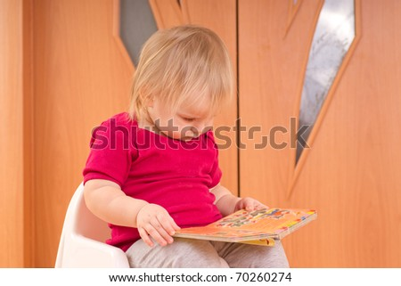 Adorable baby sit on chair and read small baby book - stock photo