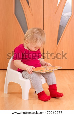 Adorable baby sit on floor and read small baby book - stock photo