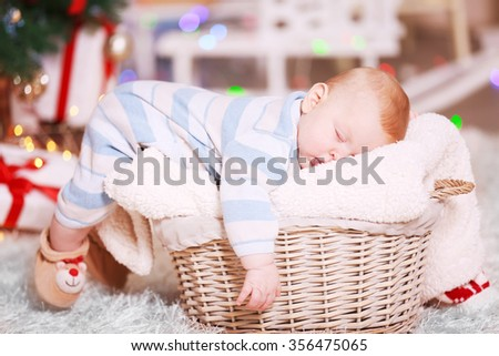 Adorable baby sleeping in decorated wicker basket - stock photo