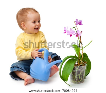 Adorable baby smiling and watering flower. Isolated on white