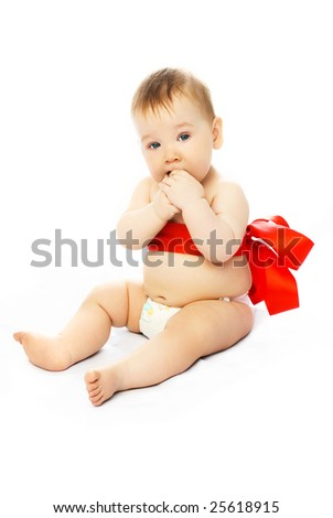 adorable baby tied up with a red ribbon sitting on the floor - stock photo
